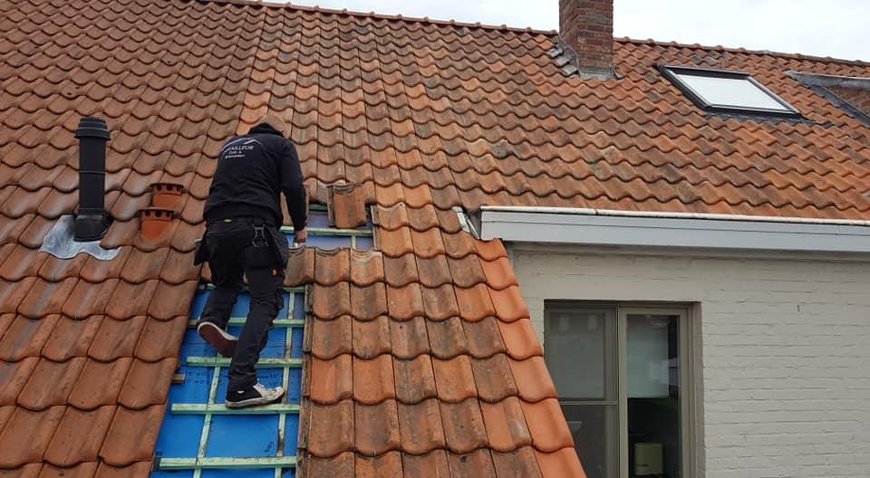 De dakdekker legt dakpannen na een dakrenovatie